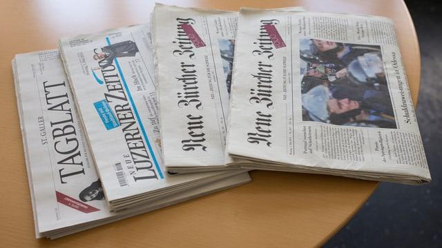 Mehrere Zeitungen auf einem Tisch.