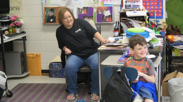 Lehrerin an ihrem Pult, ein Schüler ist auch im Bild.