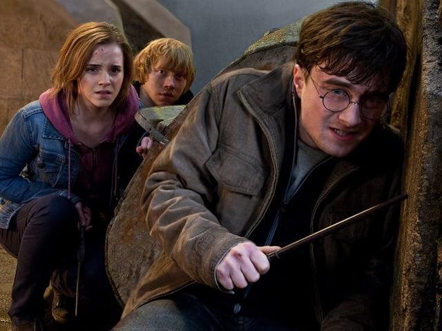 Hermine, Ron und Harry mit Zauberstab verstecken sich