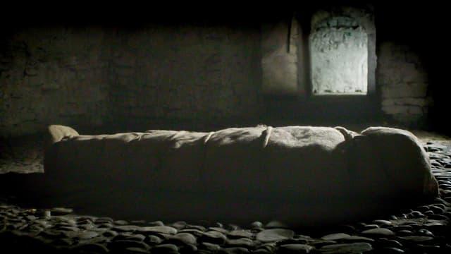Eine in ein Tuch gewickelte Gestalt in einem dunklen Raum