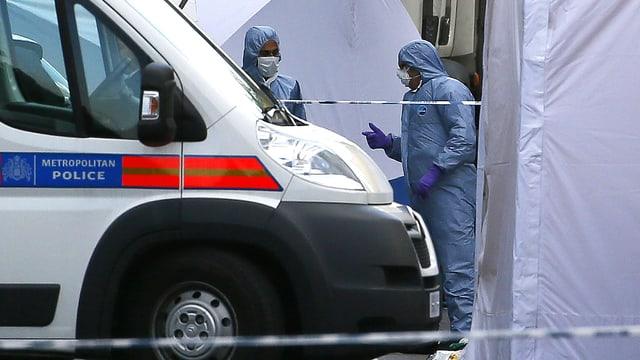 Ermittler in blauen Forensiker-Anzügen stehen hinter einem Polizeiauto. Die gesamte Szene ist mit Bändern abgesperrt.