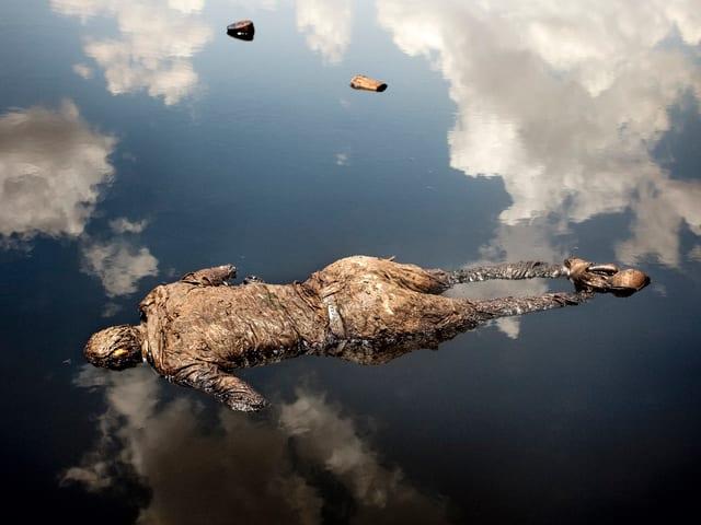 Ein Mann treibt tot im Wasser, in dem sich Wolken spiegeln.