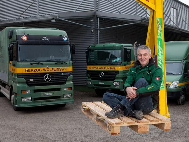 Adrian Herzog posiert vor drei Lastwagen seines Unternehmens.