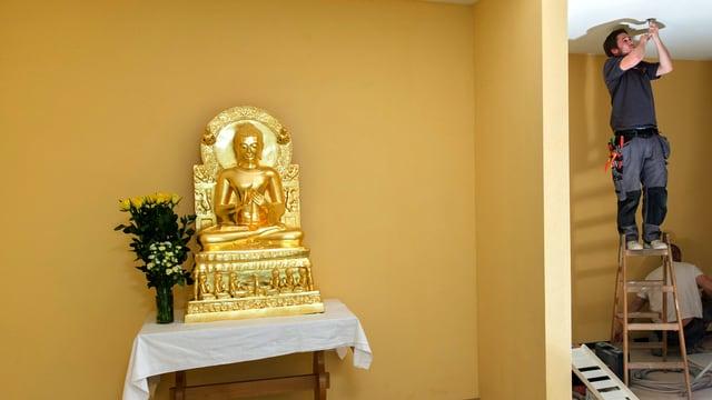 Sicht auf zwei Räume: Der eine ist aufgeräumt, auf einem Tisch mit Tischtuch steht eine Buddhastatue. Im anderen Raum ist ein Handwerker an Arbeiten an der Decke.
