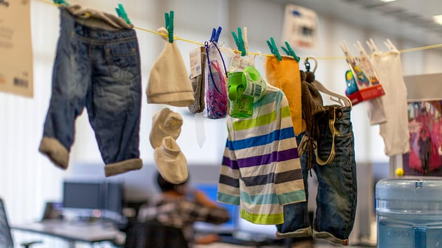 Kinderkleider an einer Leine aufgehängt in einem Büro