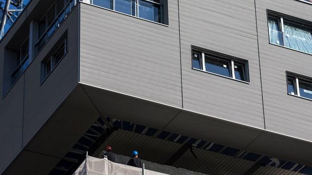 Bauarbeiter auf dem Dach des Silos geben Anweisungen, damit das Haus genau an der richtigen Stelle platziert wird.