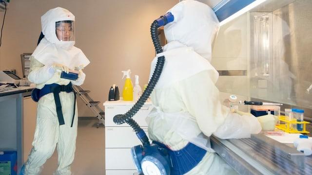 Zwei Wissenchaftler befinden sich in einem Labor und tragen Schutzanzüge mit Sauerstoffzufuhr.