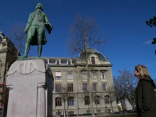 Frau steht vor einer männlichen Statue