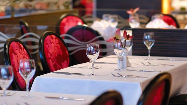 Blick in ein Restaurant, wo ein gedeckter Tisch für Gäste bereit steht.