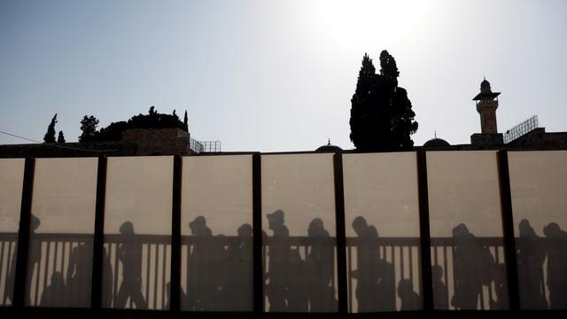 Besucherinnen und Besucher hinter einer Wand beim Tempelberg.