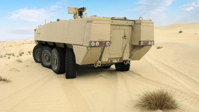 Ein sandfarbener Radpanzer in der Sandwüste.