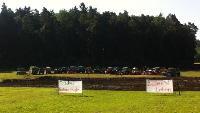 """Traktoren der protestierenden Bauern vor der aufgerissenen Wiese. Im Vordergrund zwei Transparente mit der Aufschrift: """"Flascher Naturschutz"""" und """"Boden=Leben"""""""