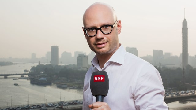 Mann steht mit einem SRF-Mikrofon im Vordergrund, hinten eine Stadt mit einem Fluss.