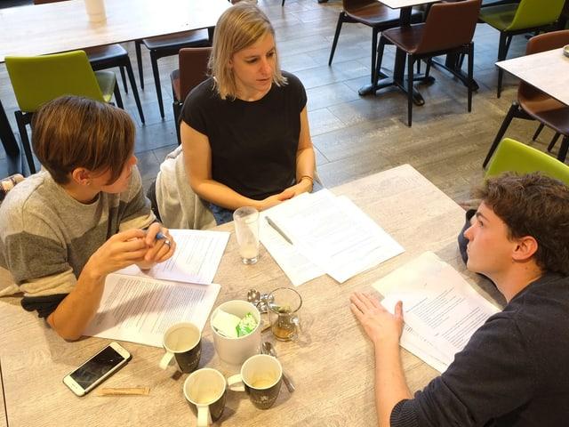 Drei Leute sitzen um einen Tisch und diskutieren.