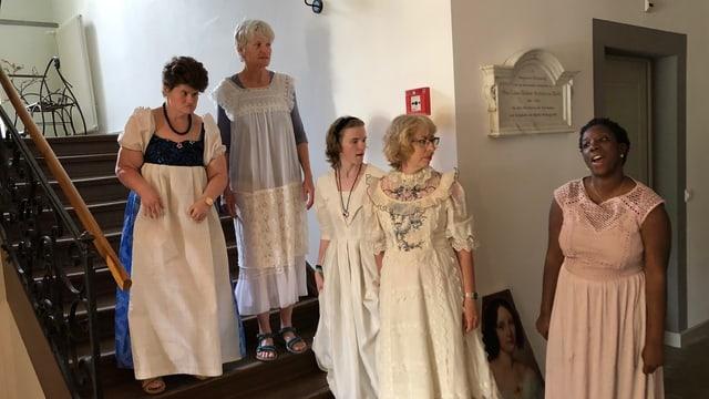 Fünf Frauen in langen Gewändern stehen in einem Treppenhaus.