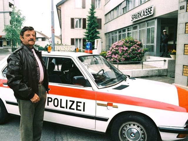 Ein Mann mit Lederjacke steht vor einem Polizeiwagen.