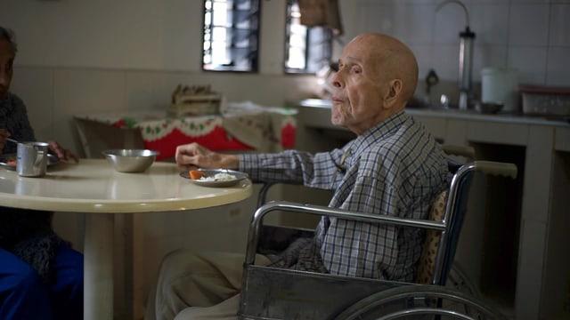 Alter Mann in einem Rollstuhl sitzt an einem Esstisch.