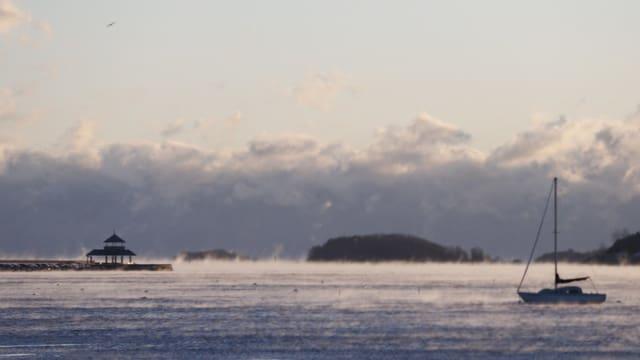 Neblig-kalte Bucht inklusive verlassenes Segelboot