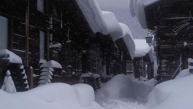 Ein Weg zwischen den verschneiten Häusern von Ulrichen.