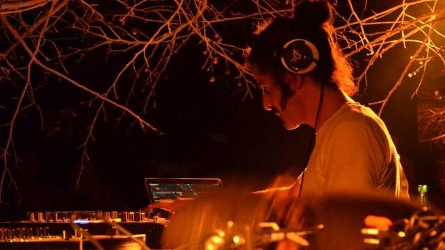Ein Mann mit Kopfhörern am DJ-Pult.
