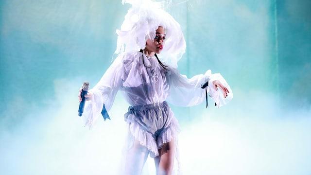 FKA Twigs auf der Bühne: sie trägt ein weisses Outfit mit pompösem, weissem Hut.