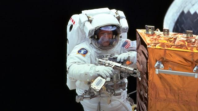 Mann in Astronautenanzug reapariert ein Weltraum Teleskop im Weltall.
