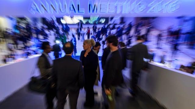 Menschen auf einer Rampe unter einer bläulichen Leuchtschrift «Annual Meeting 2016».