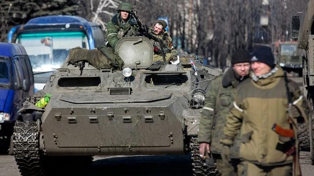 In tanc cun dus schuldads che sesan là si e dus umens en giaccas da militar cun buis chaminan sper il tanc.