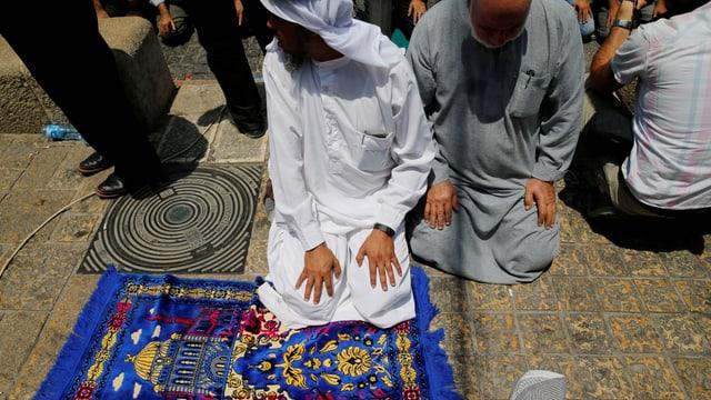 Ein muslimischer Mann in weissem Gewand, sitzt auf dem Boden neben seinem Teppich.