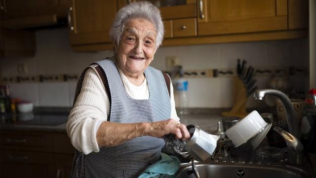 Lachende Seniorin wäscht am Spültrog eine Espressomaschine aus