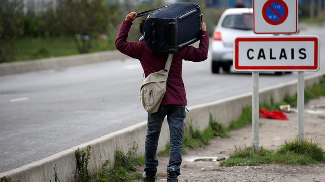 Ein Asylsuchender vor einem Calais-Schild.