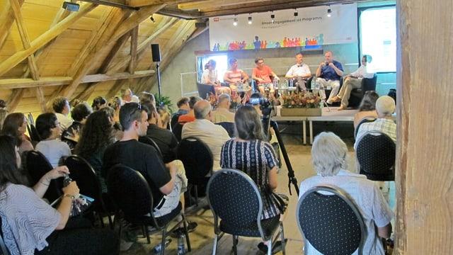 Publikum im Dachstock einer Scheune, dahinter Podium mit Schülern und Experten.