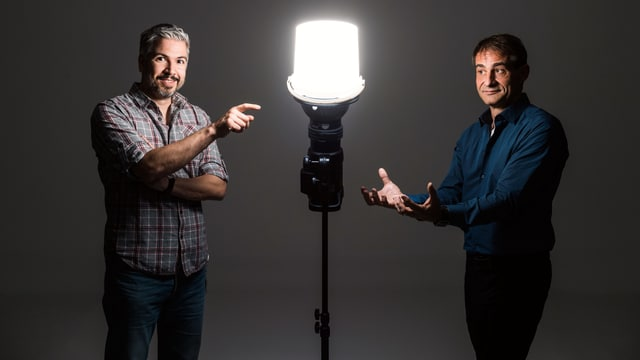 Krispin Zimmermann und Thomy Scherrer stehen um eine hell erleuchtete Lampe. Ihnen geht dabei scheinbar ein Licht auf.