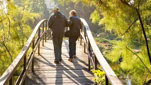 Zwei Rentner auf einer Brücke.