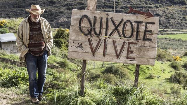 """Mann neben einem Schild mit der Aufschrift """"Quixote vive"""""""