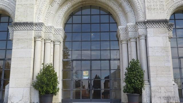 Der Eingang der Kirche mit Bögen aus weissem Stein, darin ein halbrundes Fenster, das vergittert ist.