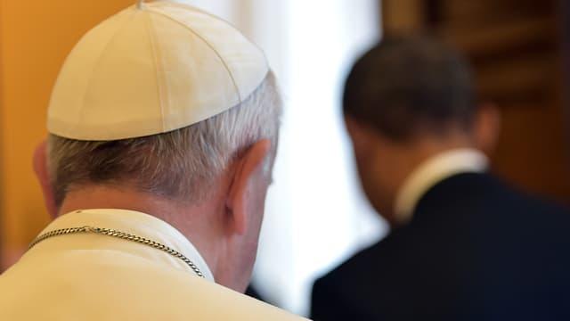 Rückenansicht der Köpfe von Papst Franziskus (links) und Barack Obama (rechts)