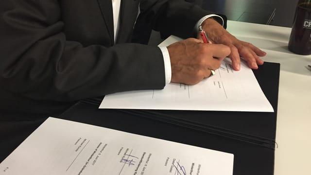 Ein Mann unterschreibt einen Vertrag.