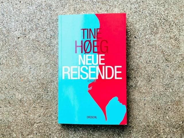 Der Roman «Neue Reisende» von Tine Høeg liegt auf einem Zementboden