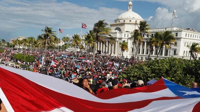 Man sieht im Vordergrund eine Fahne Puerto Ricos und im Hintergrund hunderte Demonstranten.