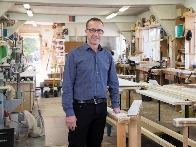 Ein Mann mit blauem Hemd steht in der Werkstatt einer Schreinerei.