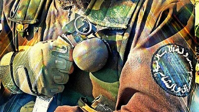 Nahaufnahme eines Al-Kaida-Kämpfers mit einer Handgranate an der Jacke.