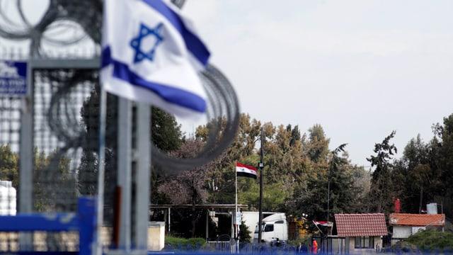 Israelisch Flagge und Grenzbefestigung, im Hintergrund syrische Flagge und Grenzposten.