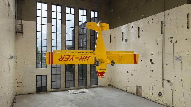 Ein gelber Kleinflugzeug hängt von der Decke einer Fabrickhalle
