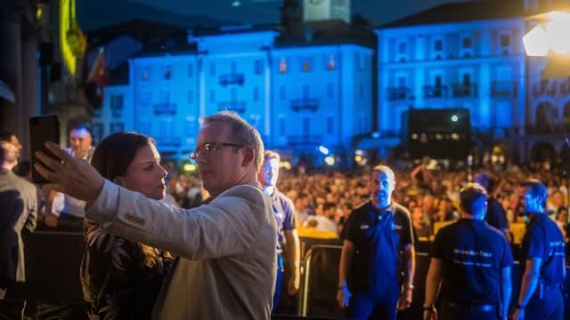 Ein Mann und eine Frau machen zusammen ein Selfie vor dem Publikum auf der Piazza Grande.
