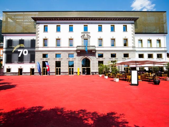 Grosses Gebäude an einem rot gefärbten Platz.