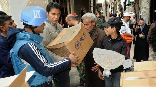 UNO-Soldaten verteilen Hilfsgüter in einem Flüchtlingslager in Damaskus.