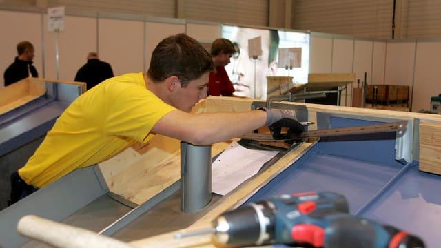 Ein junger Mann im gelben T-Shirt arbeitet an einer Werkbank.