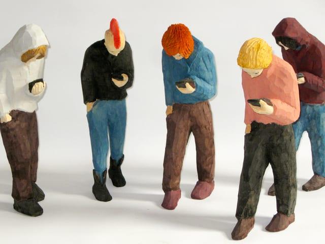 Geschnitzte Holzfiguren, die alle mit geneigtem Kopf auf ihr Smartphone schauen.