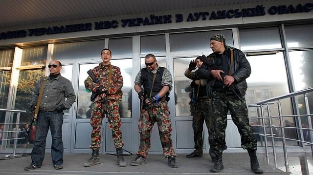 Uniformierte bewaffnete Männer stehen vor dem Eingang eines Regierungsgebäudes.